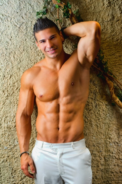 Muscular young latino man shirtless in white pants